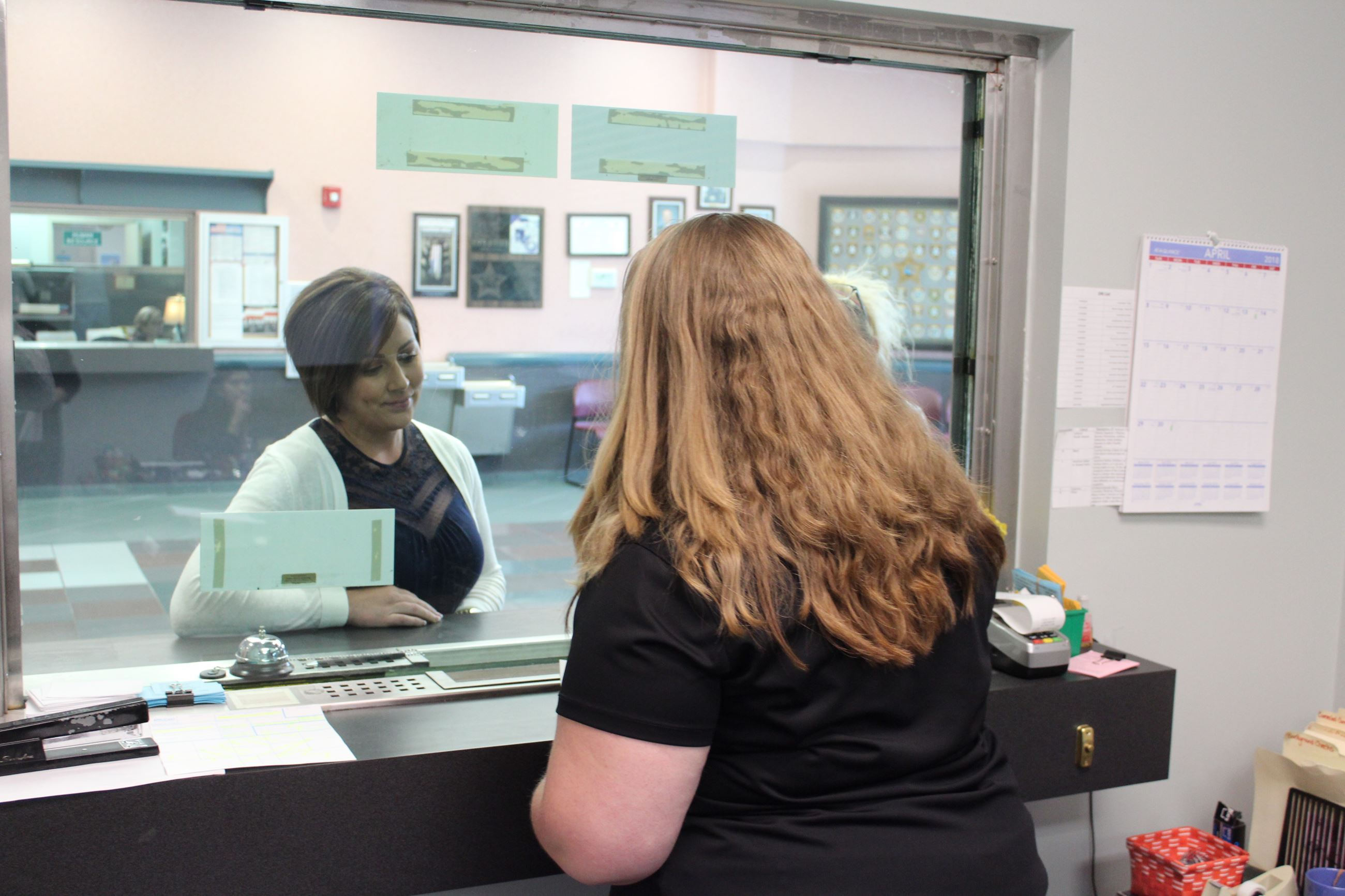Photos of clerk helping a customer at the records unit window.